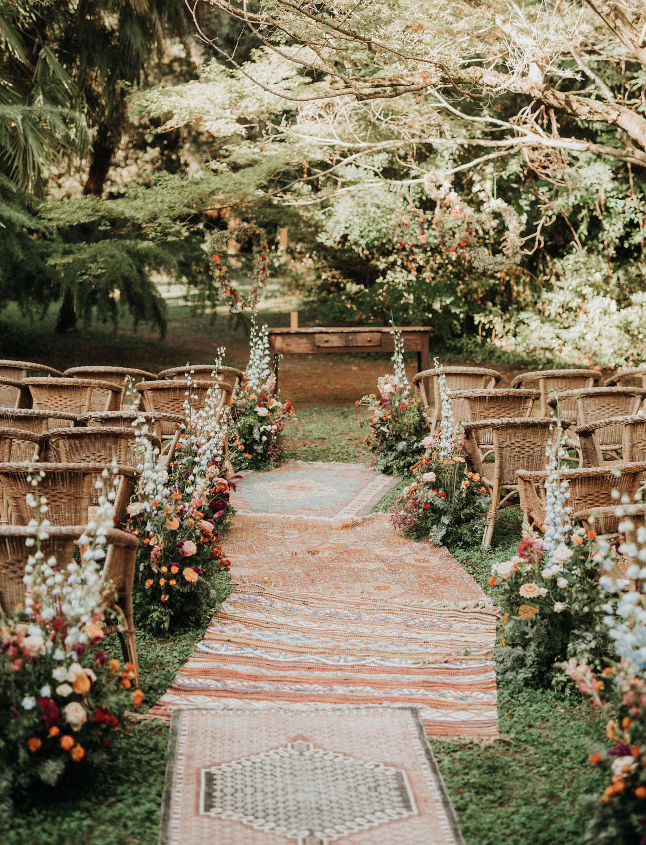 The wedding ceremony space was done super bright, with bold blooms, greenery and boho rugs