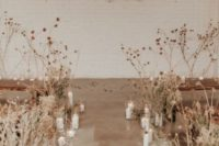 04 dried blooms and candles lining up the aisle to create a chic and ethereal wedding ceremony space