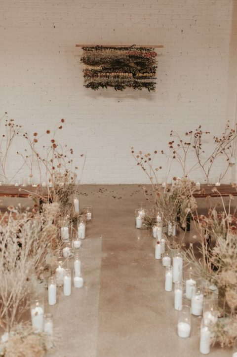 dried blooms and candles lining up the aisle to create a chic and ethereal wedding ceremony space