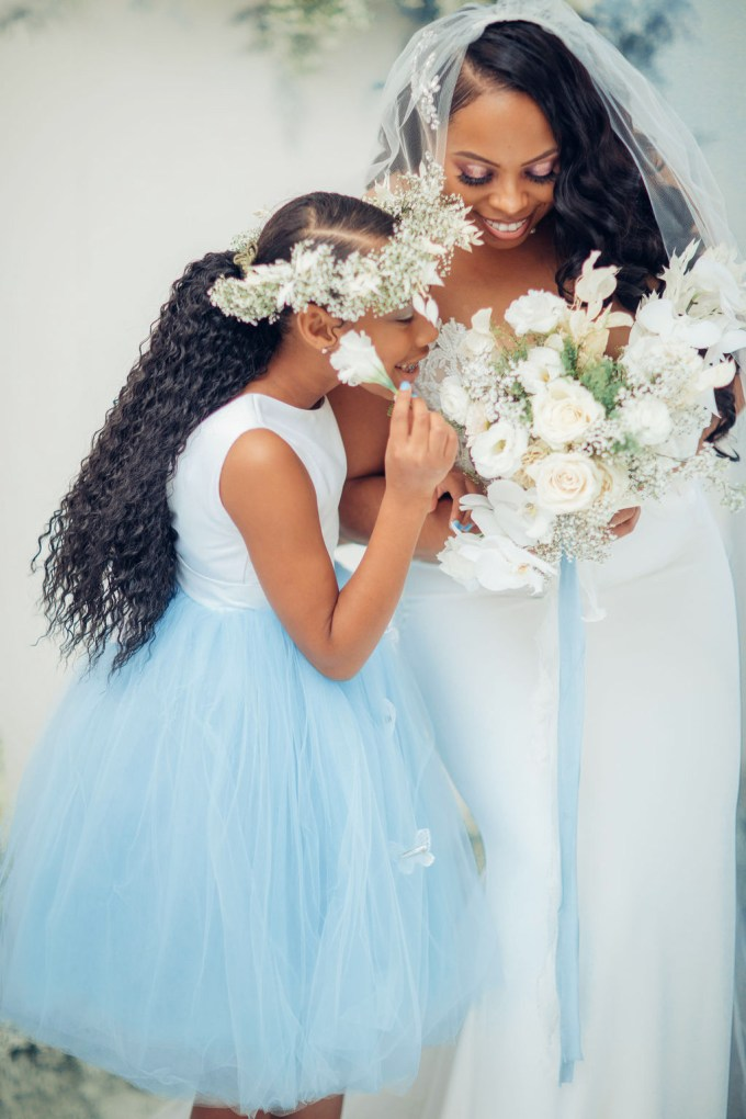 The floral girl was wearing a white and ice blue wedding dress and a baby's breath crown