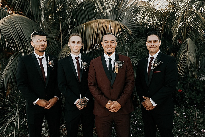 The groom was wearing a burgundy tux with black lapels, the groomsmen were rocking black suits