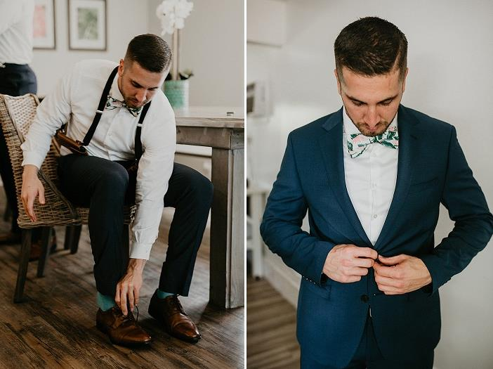 The groom was wearing a navy suit with suspenders and a bold printed bow tie plus mint socks