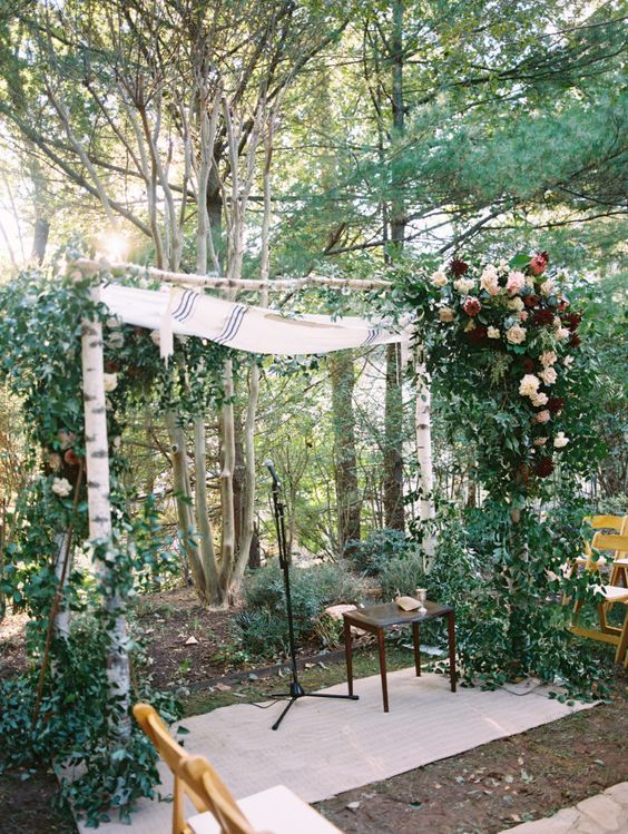 a rustic backyard wedding arch of birchwood, greenery, blush and burgundy blooms is great for a rustic and boho fall wedding