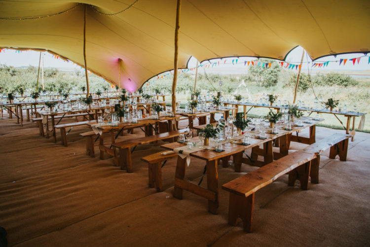 The reception was done under a large tent, with colorful buntings and wildflower centerpieces