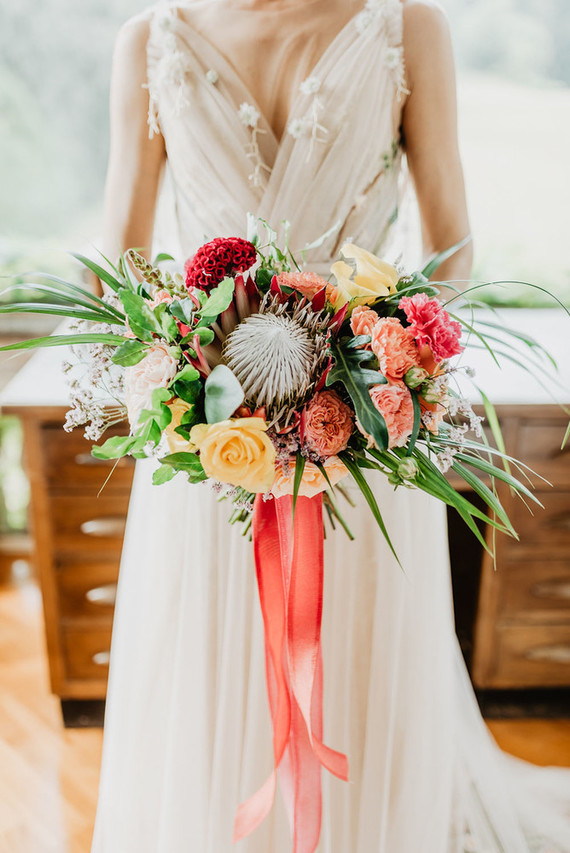 The wedding bouquet was done super colorful, with pink, burgundy and yellow blooms and greenery