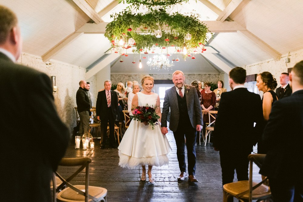 The wedding ceremony space was decorated with candle lanterns and a large chandelier with red blooms
