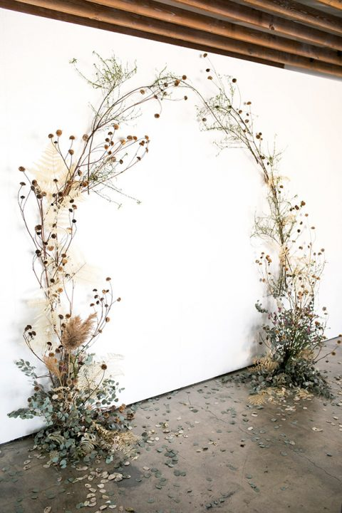 a fantastic wedding ceremony arch of eucalyptus, dried leaves and herbs plus dried billy balls