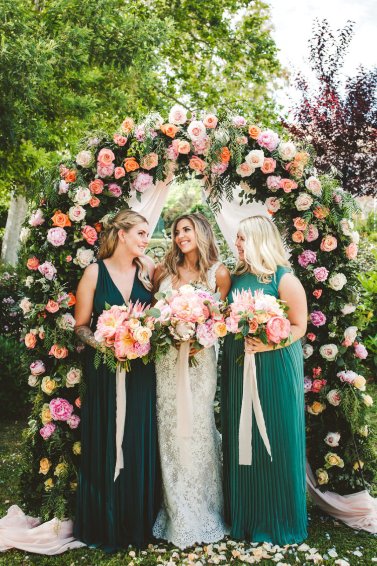 The wedding arch was decorated with greenery and bold and blush blooms all over