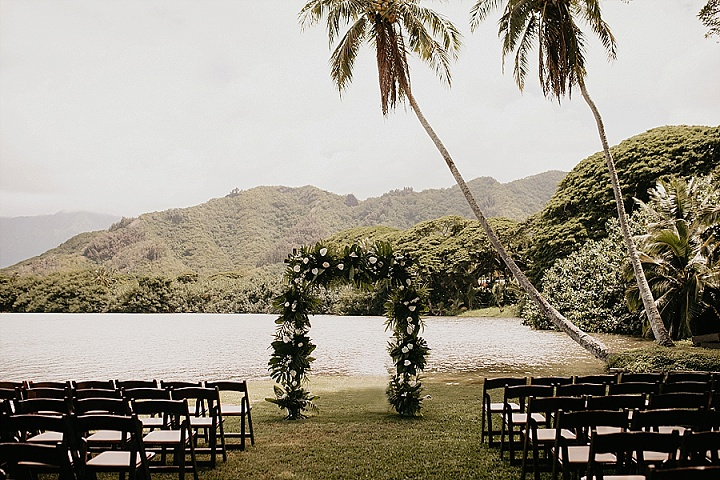 The wedding arch was done with tropical leaves and white and blooms and just look at that view