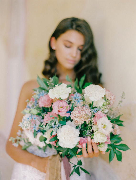 The wedding bouquet was done with neutrals, blue and pink blooms and greenery plus long ribbons