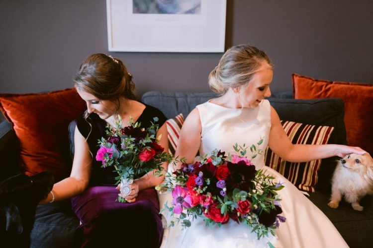 The wedding bouquets were done with red, fuchsia and dark purple blooms and greenery