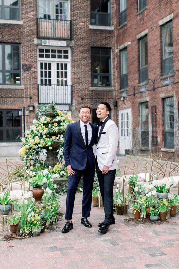 The wedding ceremony space was a non-working fountain with lush blooms and potted blooms and white chairs