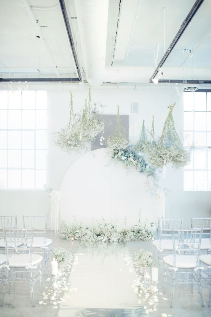 The wedding ceremony space was done with sheer chairs, lots of white candles and blooms, a round backdrop and florals hanging over the space