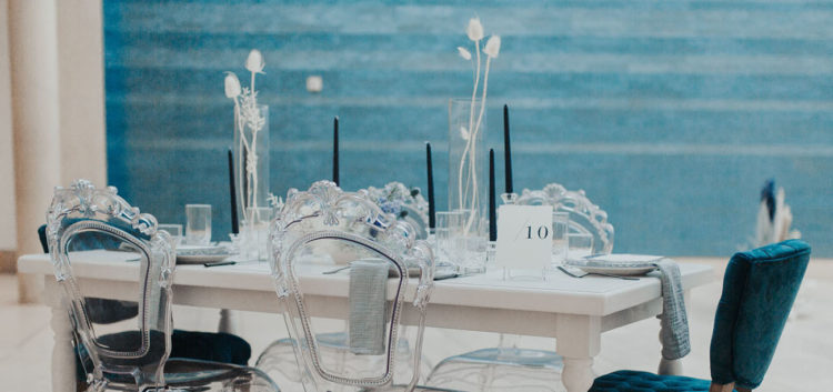 The wedding tablescape was done with black candles, dried white blooms and grasses, elegant chairs and grey linens