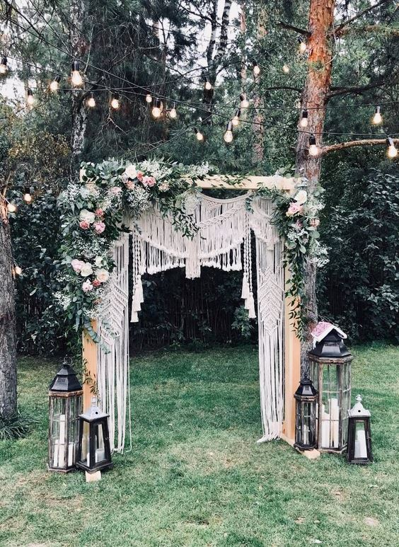 a gorgeous boho backyard wedding arch with macrame, greenery, pink and white blooms and oversized vintage candle lanterns
