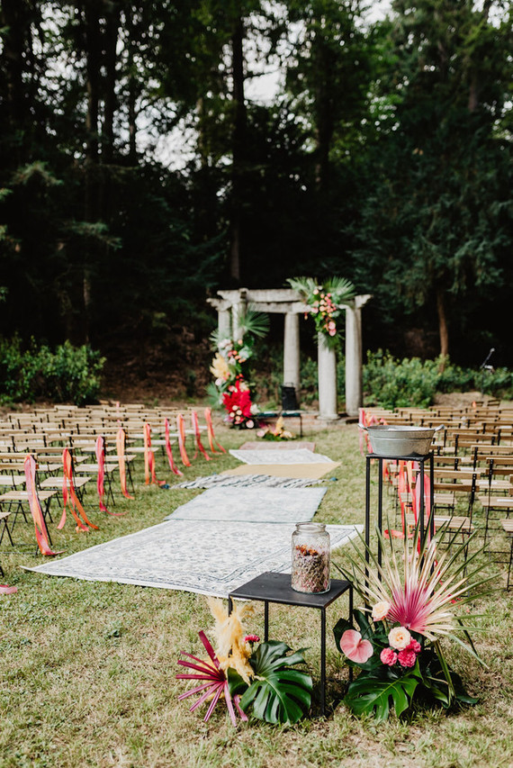 The chairs were decorated with pink ribbons, and there were boho rugs, lush florals decorated the space