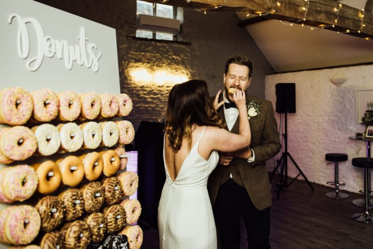 The couple went for a glazed donut wall instead of a traditional wedding cake