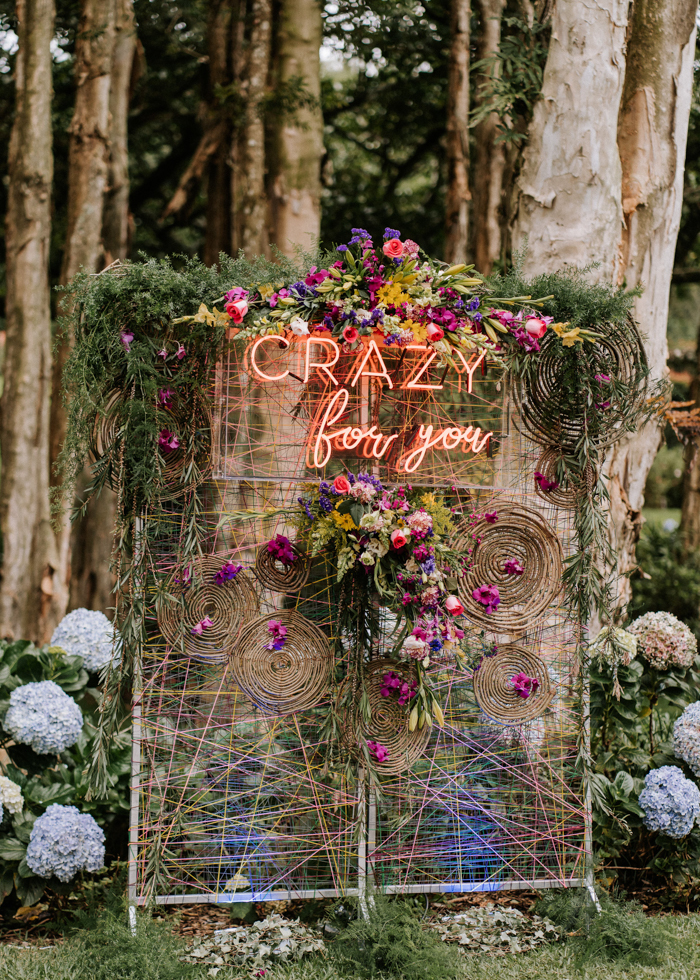 The wedding backdrop was done with colorful yarn and blooms, with a neon sign and greenery on top