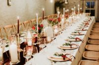 08 The wedding tablescape was done with a burgundy velvet runner, red and white candles, greenery and red blooms and matching chandeliers and wooden chargers