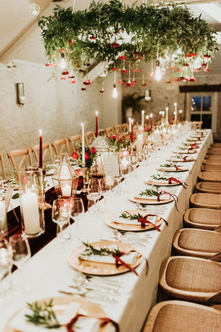The wedding tablescape was done with a burgundy velvet runner, red and white candles, greenery and red blooms and matching chandeliers and wooden chargers