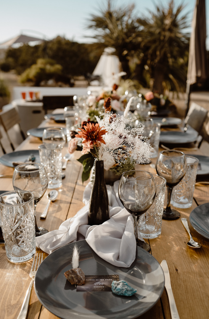 The wedding tablescape was done with a white table runner, muted color blooms, rocks, pampas grass and chic glasses