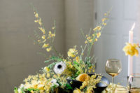 08 The wedding tablescape was done with a yellow tablecloth, lush white and yellow blooms and greenery, black porcelain and sheer plates