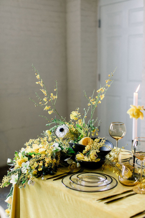 The wedding tablescape was done with a yellow tablecloth, lush white and yellow blooms and greenery, black porcelain and sheer plates