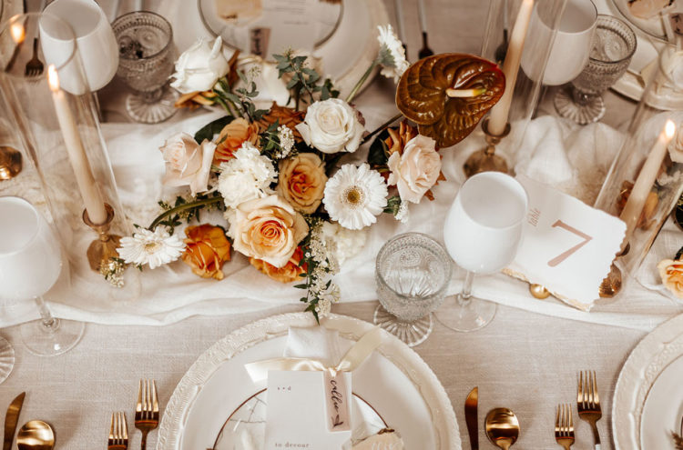 The wedding tablescape was done with peachy and gilded blooms, candles, copper cutlery and and other touches