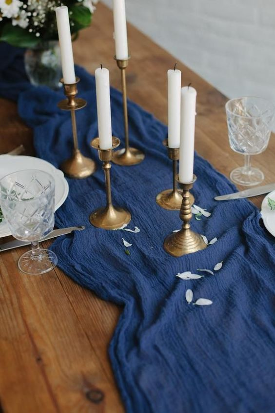 a bold blue gauze table runner like this one can substitute a floral or greenery table runner