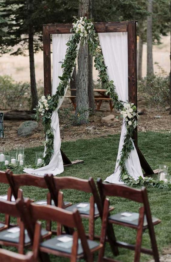 a dark stained wedding arch with white curtains, greenery and white blooms, white candles and stained chairs