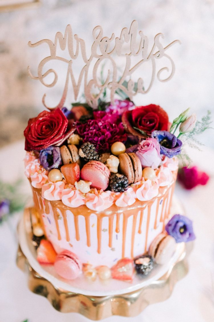 The wedding cake was colorful, pink with chocolate drip, pink and neutral macarons, red and purple blooms, a calligraphy topper and berries