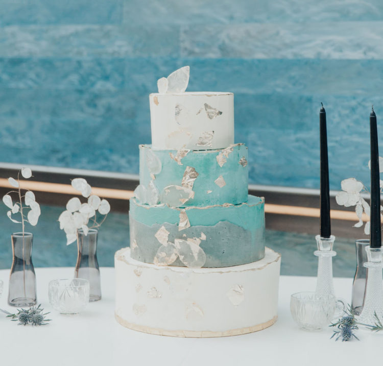 The wedding cake was done with white and blue tiers, with silver edges and edible glass
