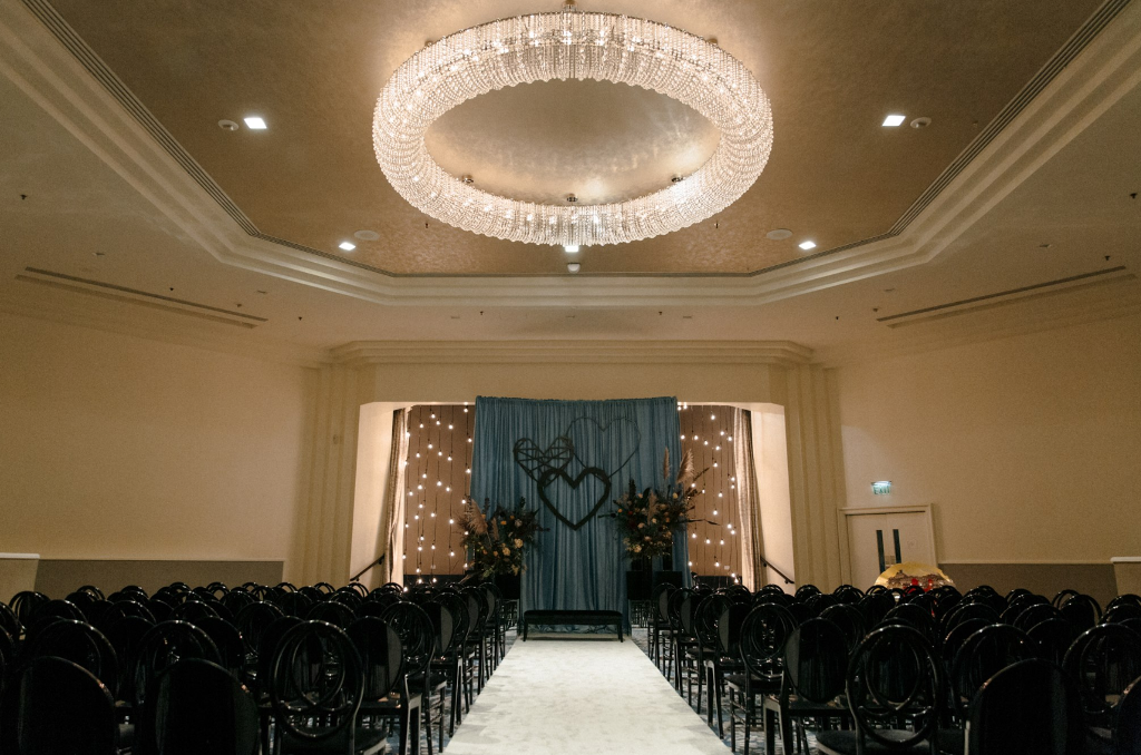 The wedding ceremony space was done with black chairs and vases with pampas grass, greenery and blush blooms