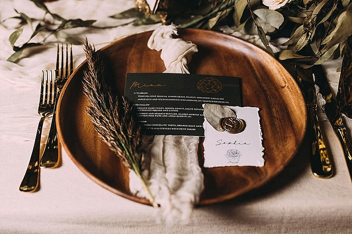 Wooden chargers, grasses, light napkins and chic gold cutlery made the tablescape cooler