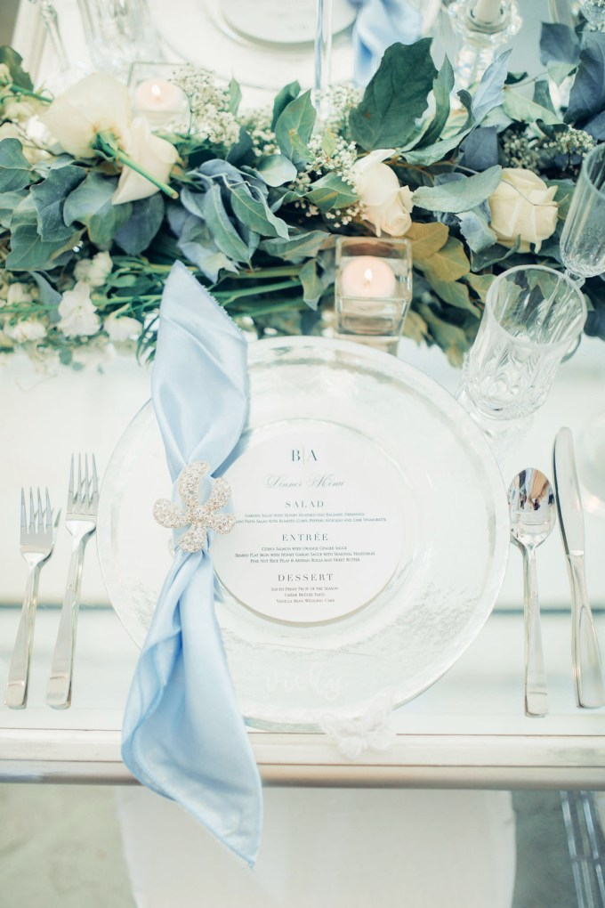 The wedding table runner was done of white blooms, greenery and candles, a silver charger and a blue napkin