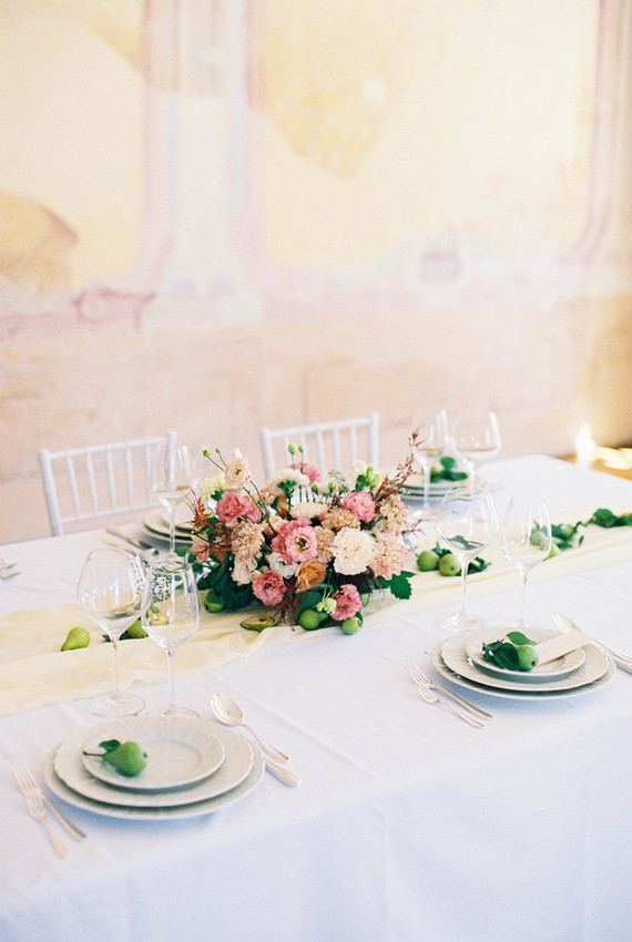The wedding tablescape was done in neutrals, with a pink floral centerpiece, green fruit, neutral textiles and cutlery