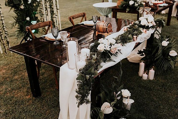 The wedding tablescape was done with greenery, white blooms and candles, the table was uncovered