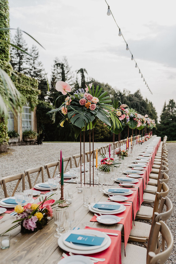 The wedding tablescape was done with pink mats, lush tropical florals and leaves, blue menus and colorful candles