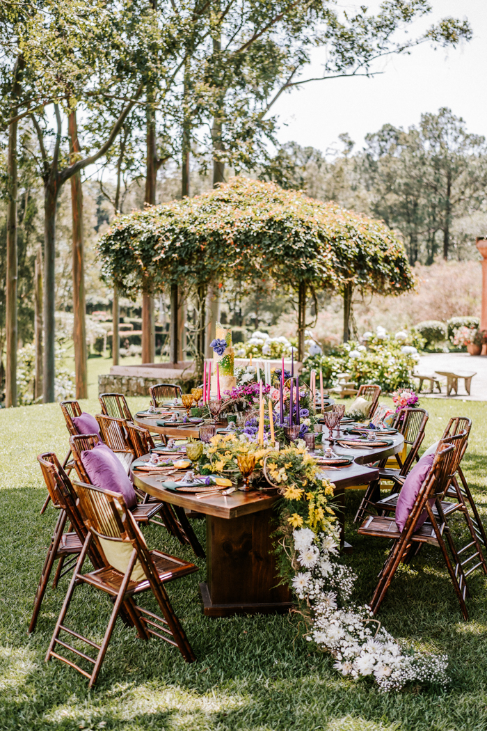 The wedding tablescape was wow, with a floral runner, colorful candles and colorful glasses