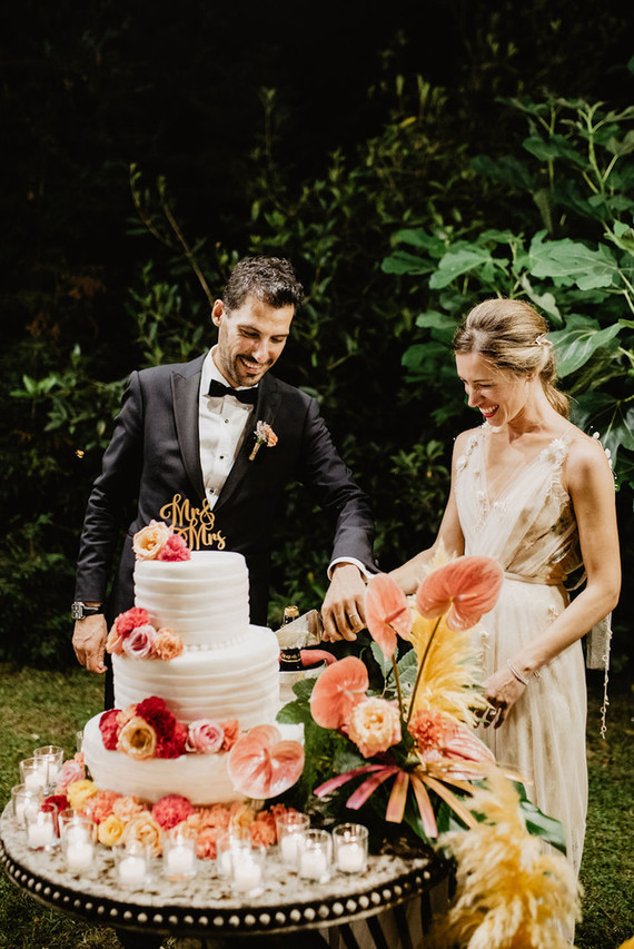 The wedding cake was a white textural one, with colorful blooms and candles and pampas grass around