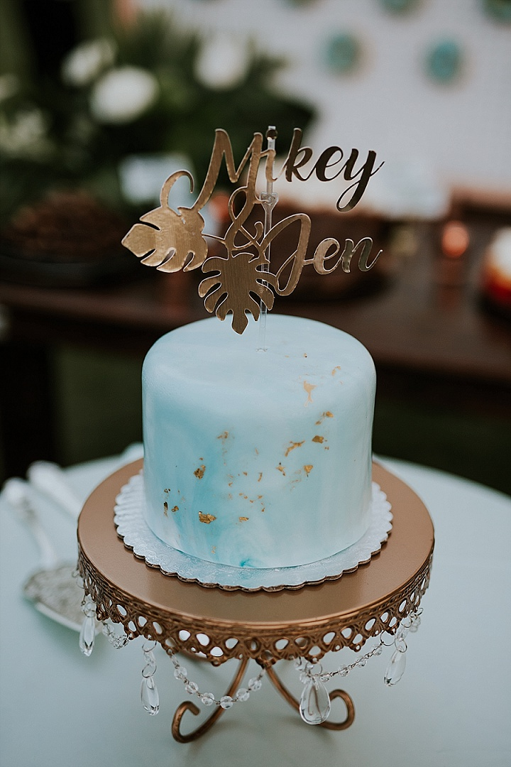 What a lovely blue watercolor wedding cake with a gold topper and gold leaf