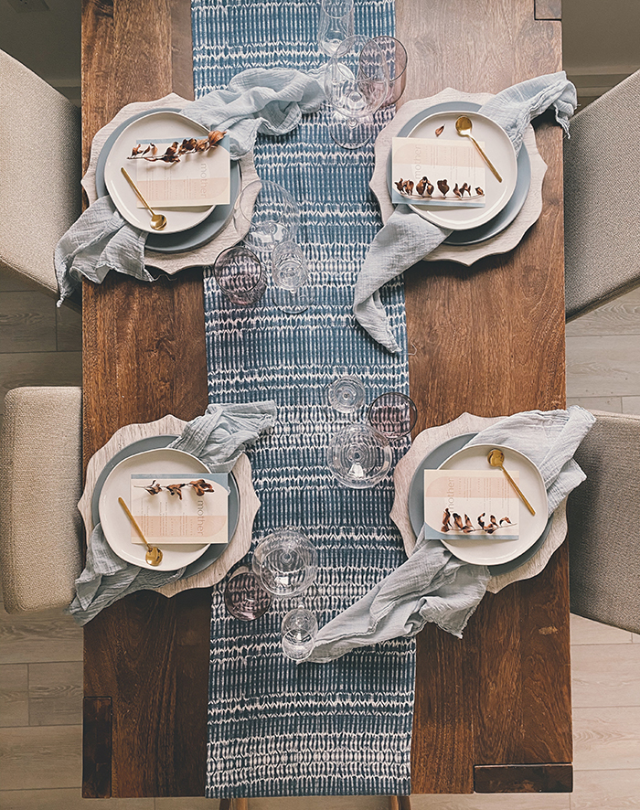 a printed blue table runner, matching light blue napkins and chargers create an ethereal and chic tablescape