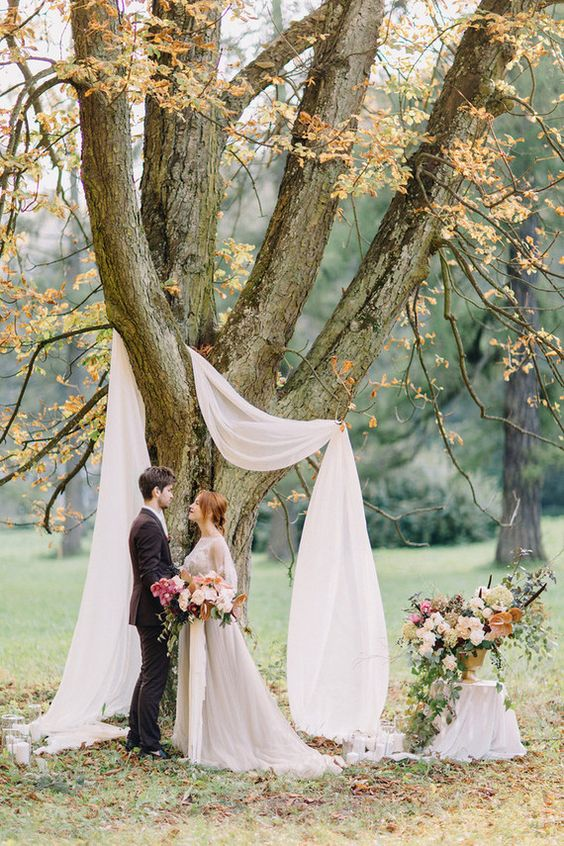 a simple wedding arch using a living tree and some airy white fabric with candles and fall leaves on the ground
