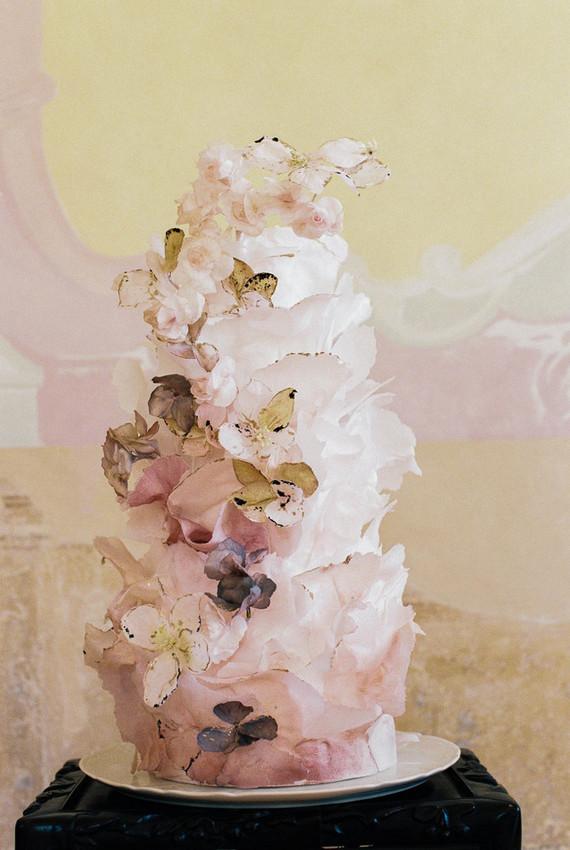The wedding cake was a blush and white one, with layers and petals, with blooms