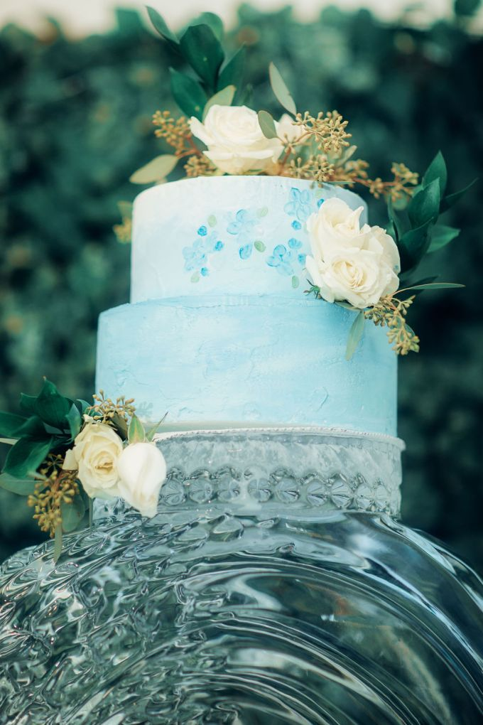The wedding cake was icy blue, with painted and fresh blooms