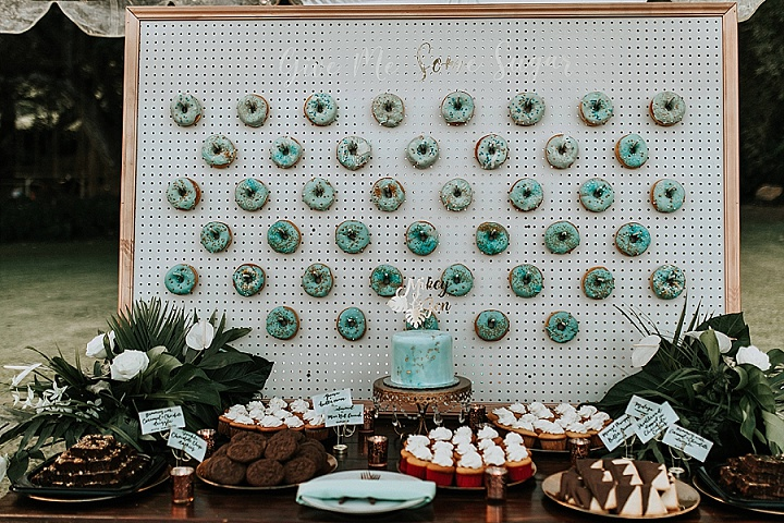 The wedding dessert table included a trendy wedding donut wall, with mint glazed donuts