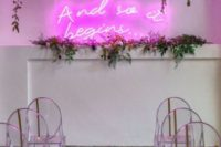 12 a chic modern wedding ceremony space with a pink neon sign, greenery, hanging blooms and acrylic chairs