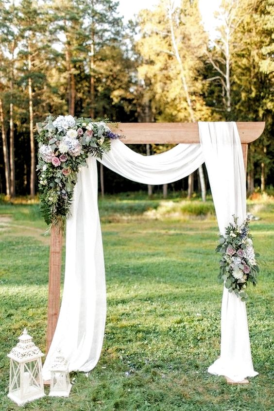 an elegant rustic backyard wedding arch with airy fabric, pastel and white blooms, greenery and white candle lanterns