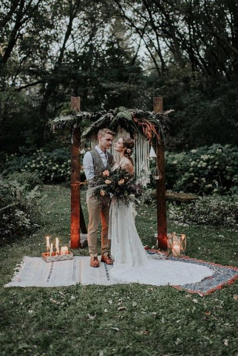 a boho backyard wedding arch with geometric candle lanterns, lush greeneyr and branches and macrame decor plus layered boho rugs