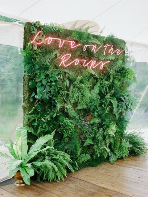 a lush greenery wall with a red neon sign is a very fresh and cool wedding decor idea